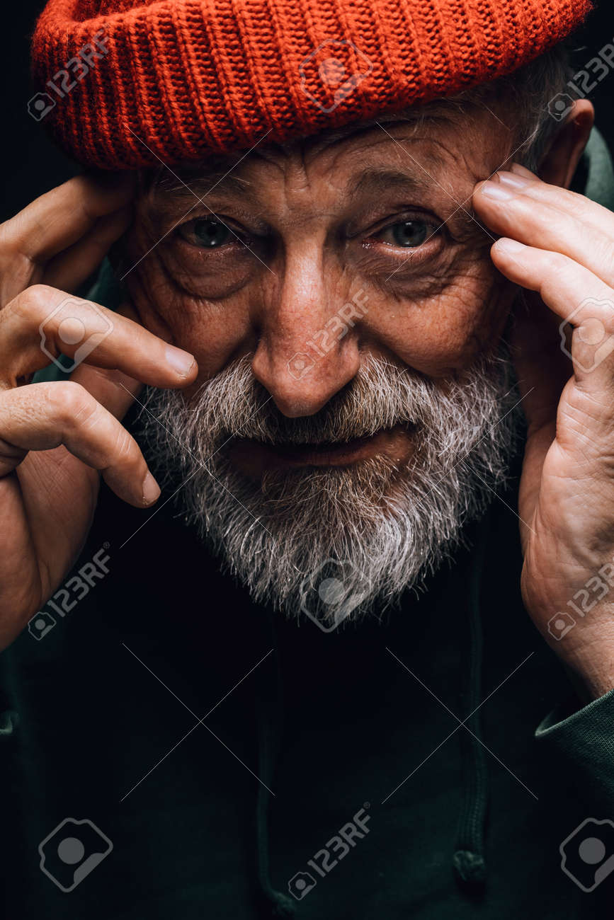 Close up portrait of bearded old man in orange hat with wrinkled weathered face stares hopefully at camera holding hands near the temples, isolated over black background. Human emotions concept. - 154138093