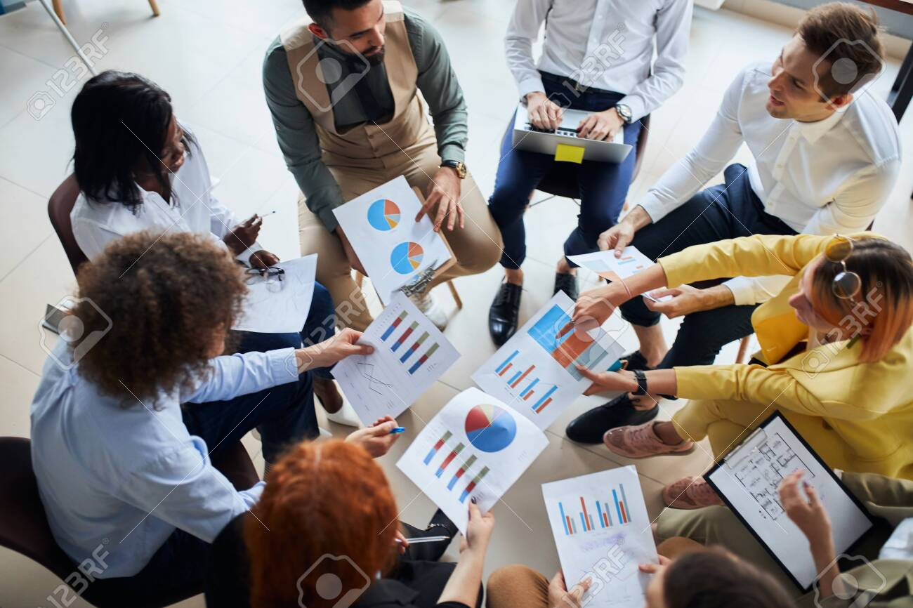 Multi-cultural business team gathered to discuss business startup in modern office, sit together in circle holding papers with diagrams - 154586461