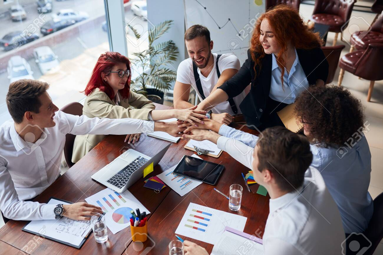 Positive group of co-workers joined hands together finishing up successful business meeting in conference office, papers, colorful pencils on table. Creative workers - 154586543