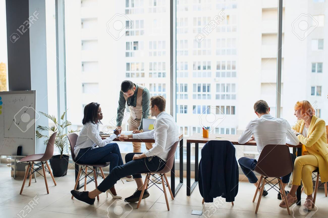 Executives having friendly discussion during break, business ideas, building business strategy while sititng on table together . office background - 154512254