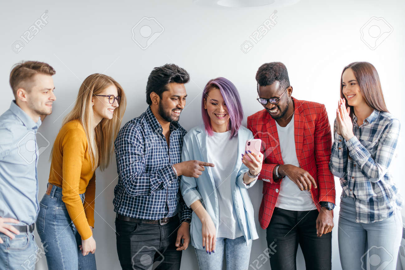 Group of Multicoloured joyful people standing against white wall. Caucasian woman with violet hair showing photos on smartphone to her diverse friends. Technology concept with young users people. - 155091095