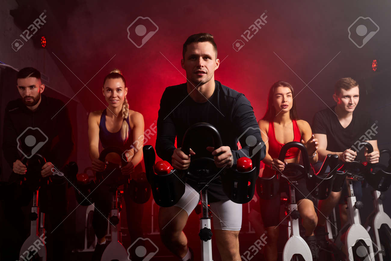 athlete people workout ride a bike in gym, with the intention of healthcare. caucasian men and women ycling to make body healthy with tight muscles and reduce the weight. male in the center - 169212142