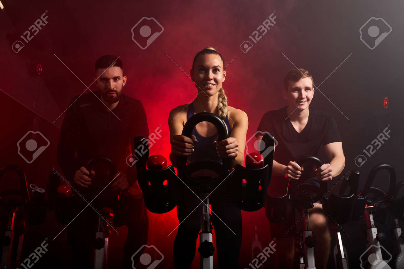fit people riding exercise bikes in gym, enjoying workout time, in smoky red neon space - 169212143