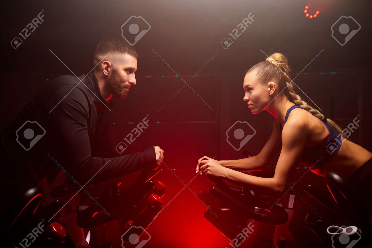 male and female sport people hold competition on bike in gym isolated on red neon lighted smoky space, oppsite of each other - 169212149