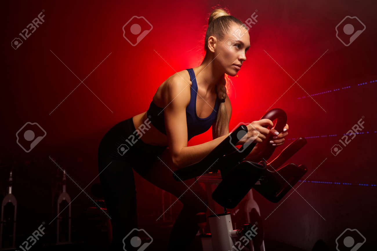 blond woman on bicycle working out at gym in smoky space, concentrated on workout - 169212151
