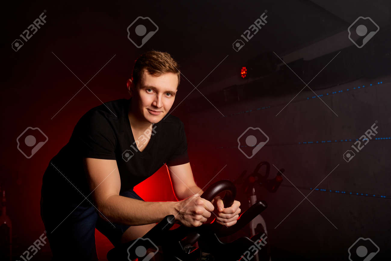 male sitting on bike in gym posing at camera, workout ride a bike in gym, with the intention of healthcare - 169212517