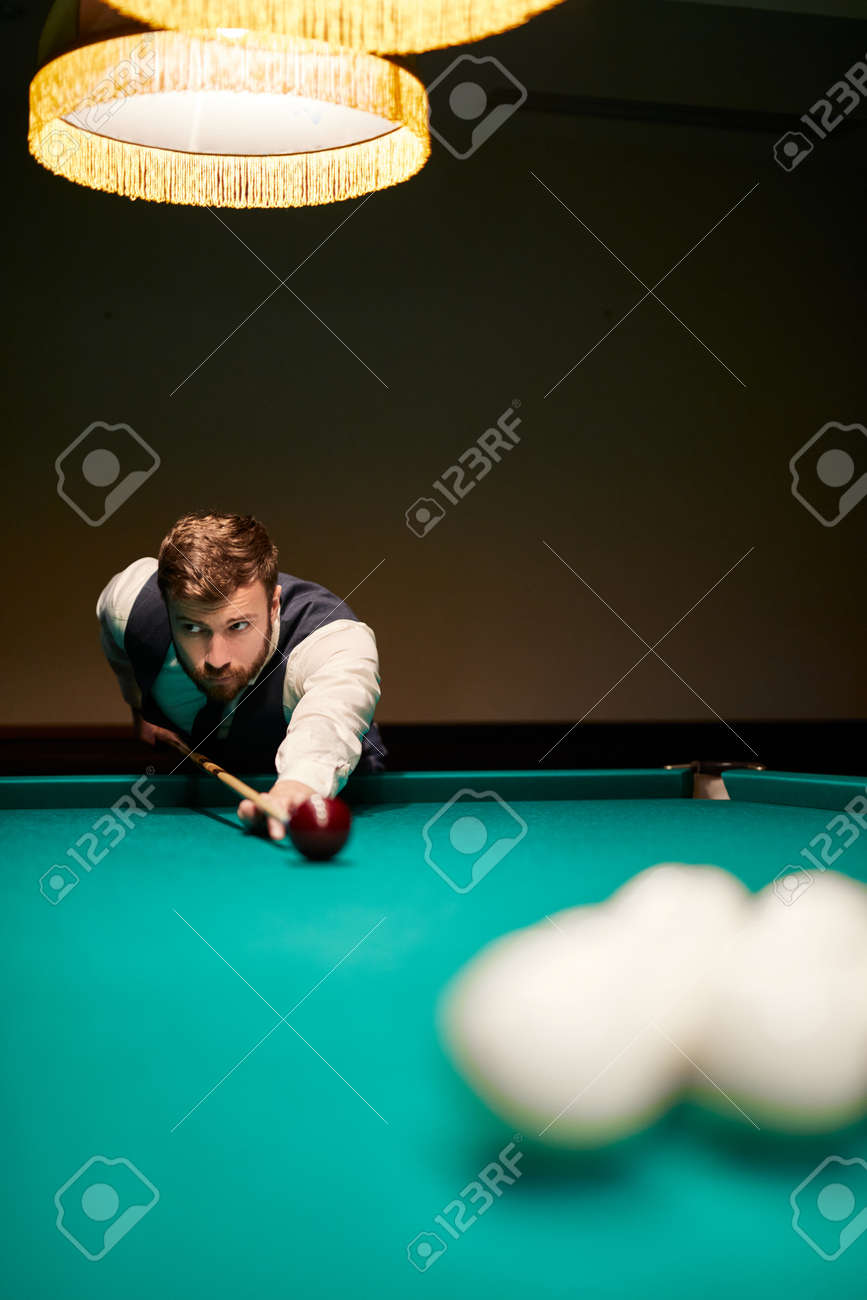 man leaning over the table while playing snooker, he is concentrated on game, having leisure time - 169212524