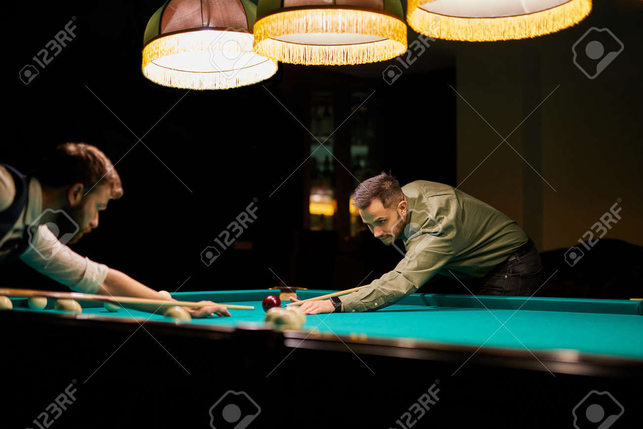 group of people or friends playing fun billiards, snooker or pool together, enjoy leisure time. fun, billiards, leisure, rest concept - 169212525