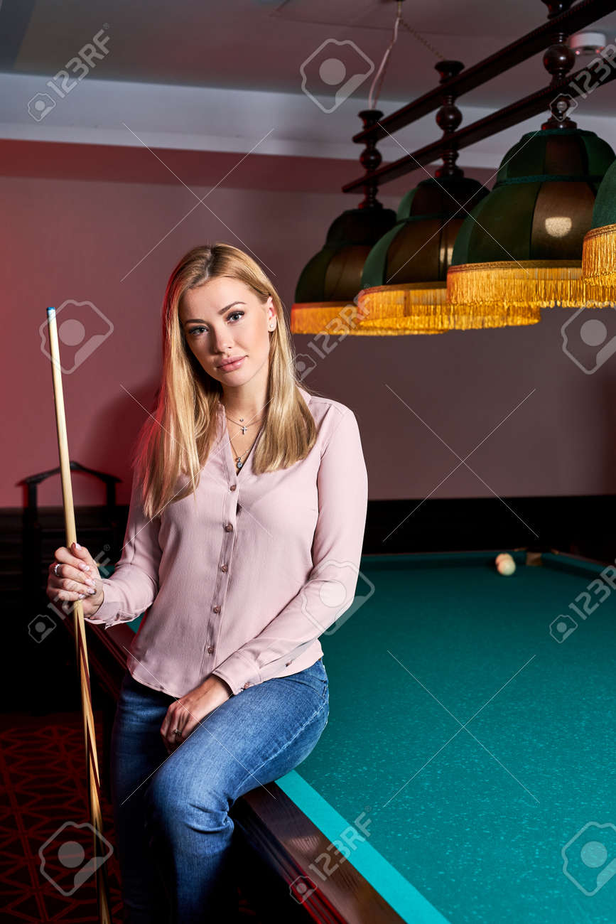 blond female came to spend pleasant time playing snooker, she is posing at camera, sitting on pool, billiards table - 169212536