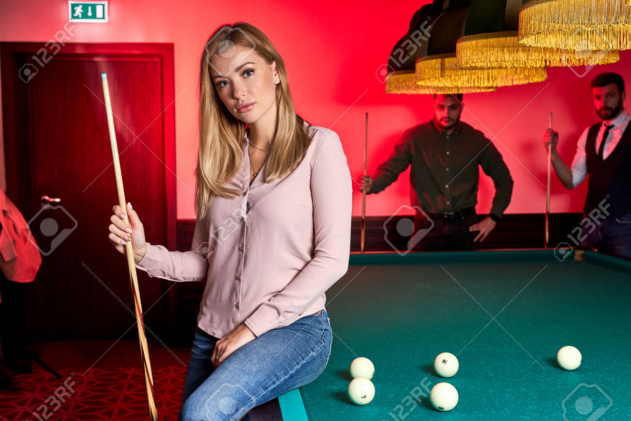 portrait of blond female sitting on billiard table posing, wearing casual outfit, in the bar, spending pleasant time, holidays - 169212537
