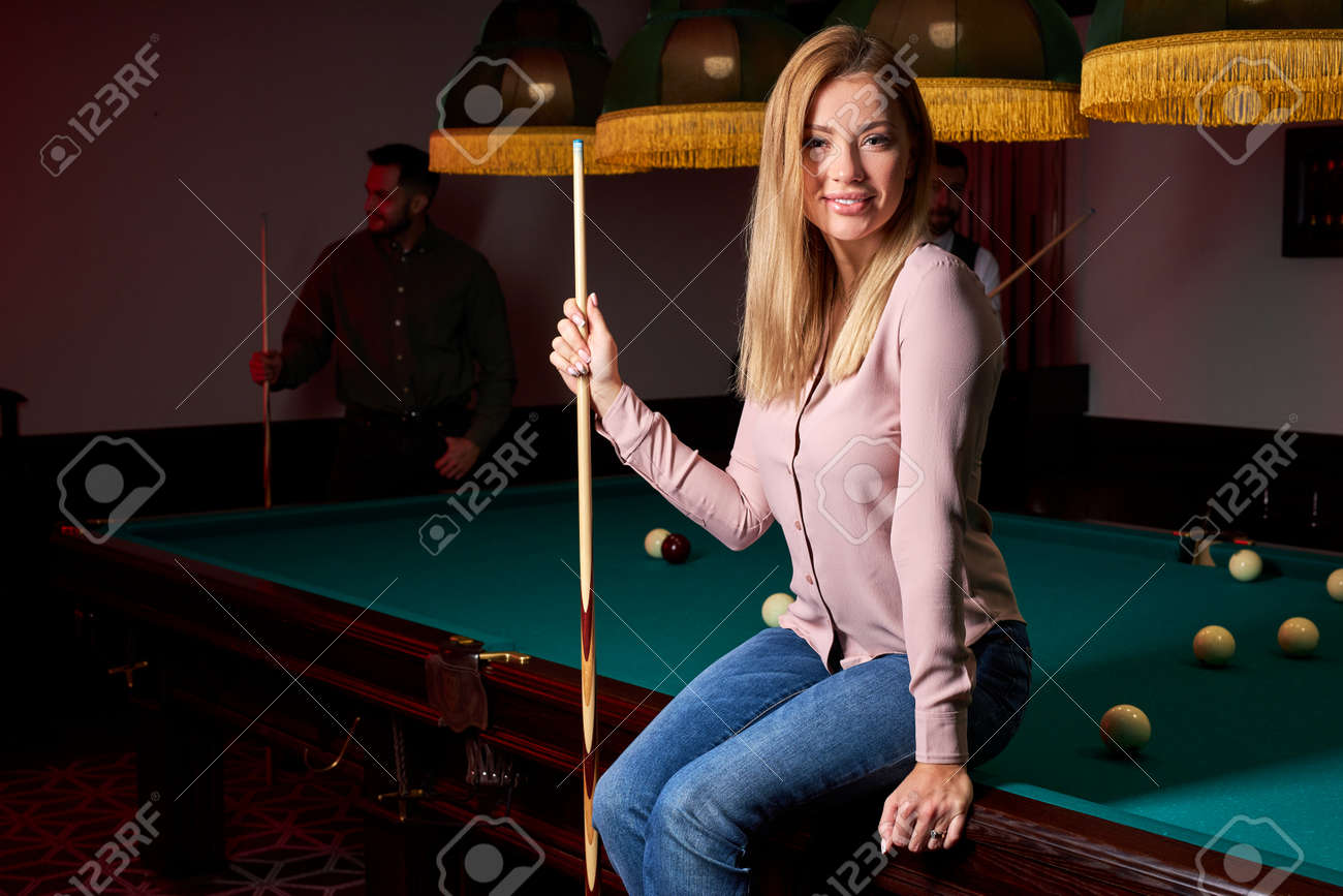 pretty woman in the bar next to billiards table pool, people playing snooker in the background. portrait - 169212540