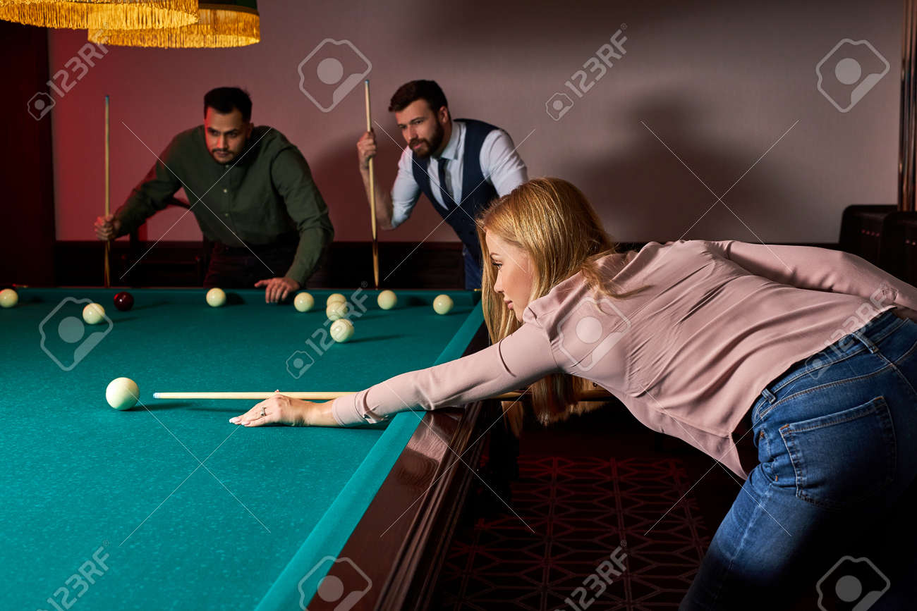 woman playing snooker, she is aiming to shoot the snooker ball, holding hands on snooker table. billiards - 169212620