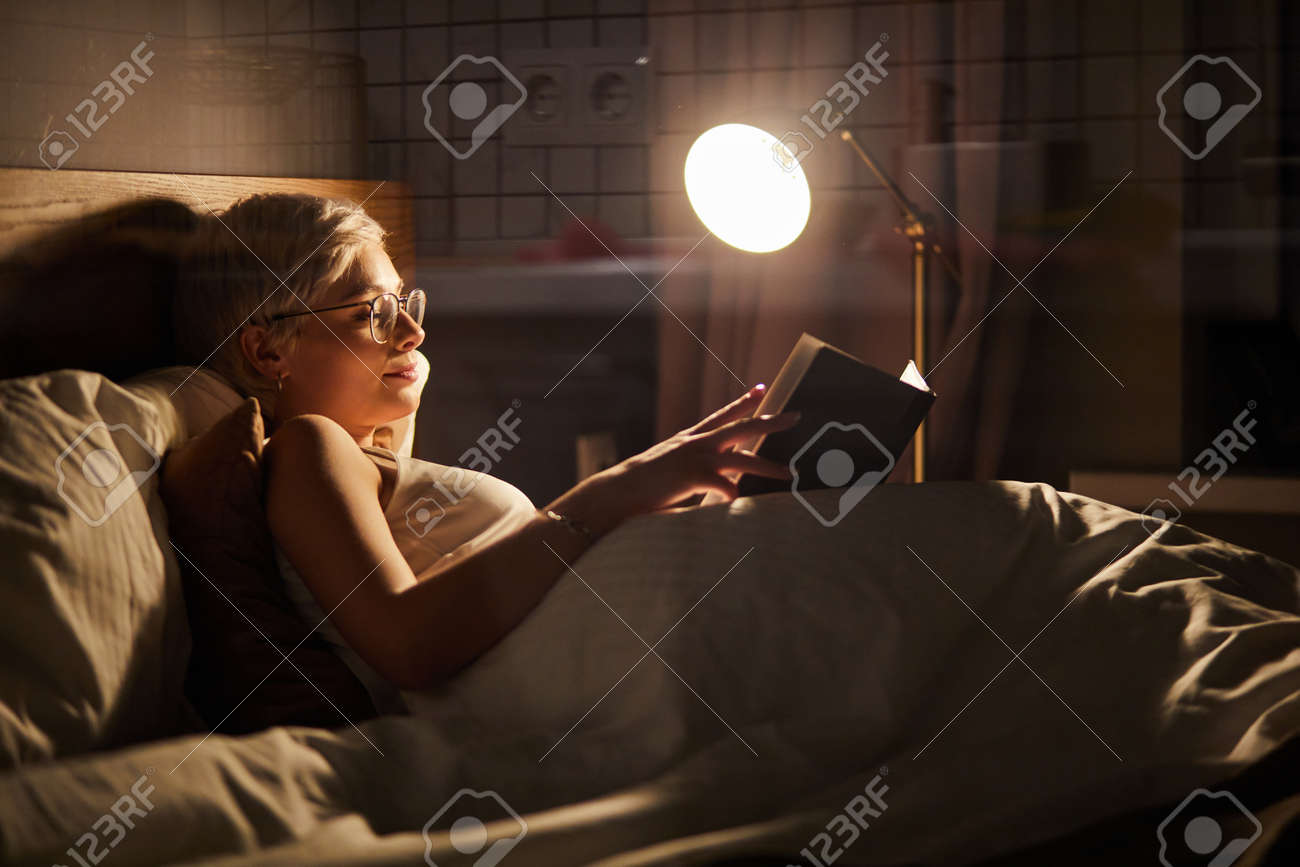 Beautiful female in pajamas and eyeglasses lying on bed reading book, alone at night. Caucasian short haired lady in bedroom, charming cute woman in room lighted by lamp - 169368811