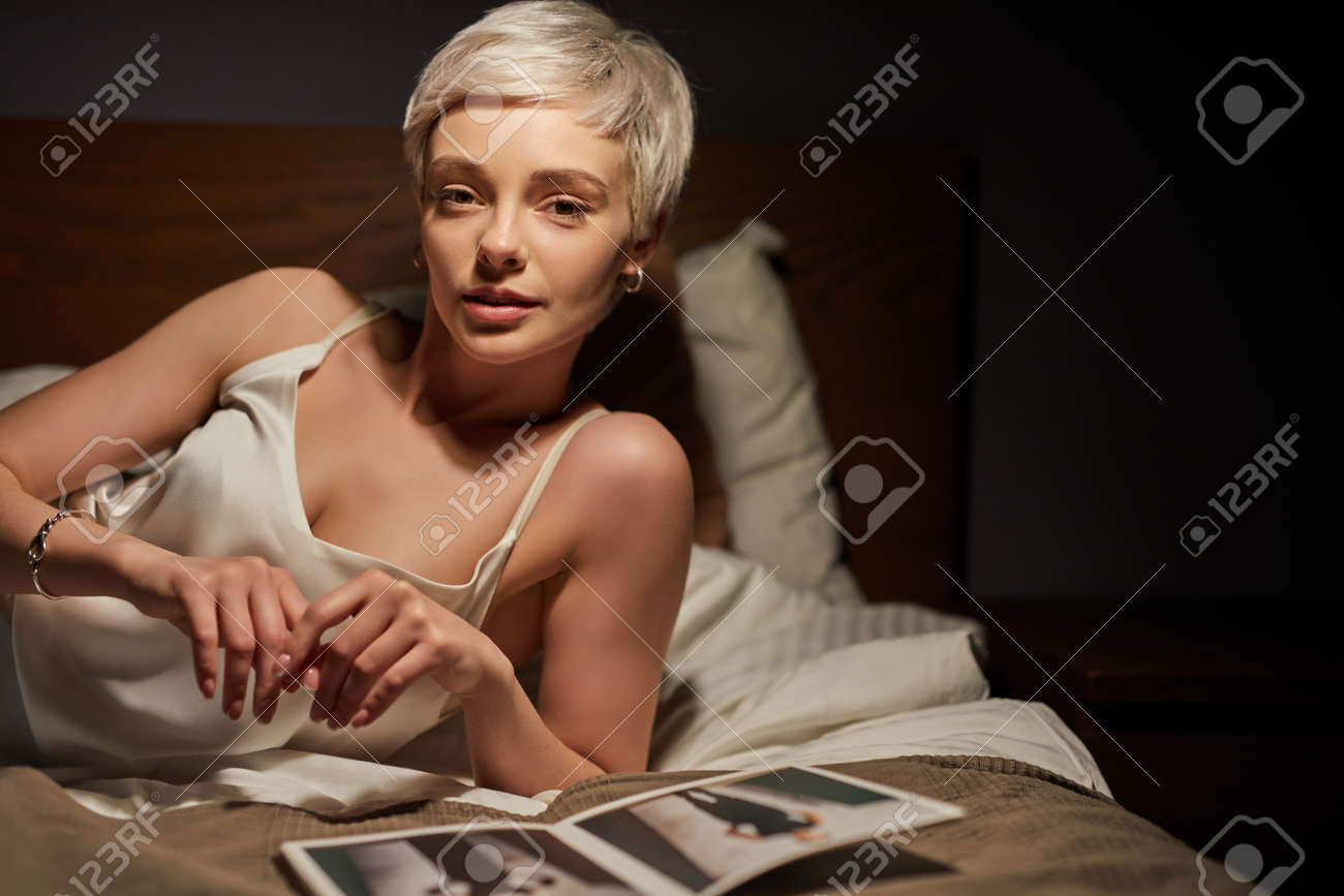 Portrait Of Stylish Lady Lying On Bed Alone, With Magazines Photos On Bed. Elegant Woman Of Caucasian Appearance Having Rest - 169368810