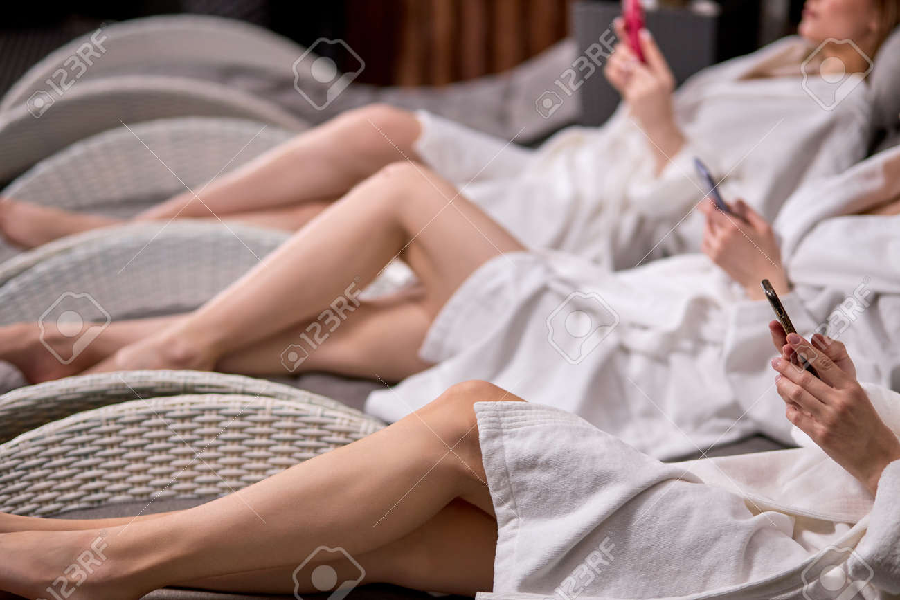 Side view on cropped women with smartphone in spa center, wearing bathrobes, unrecognizable ladies chatting, surfing the Net after beauty procedures - 169368933