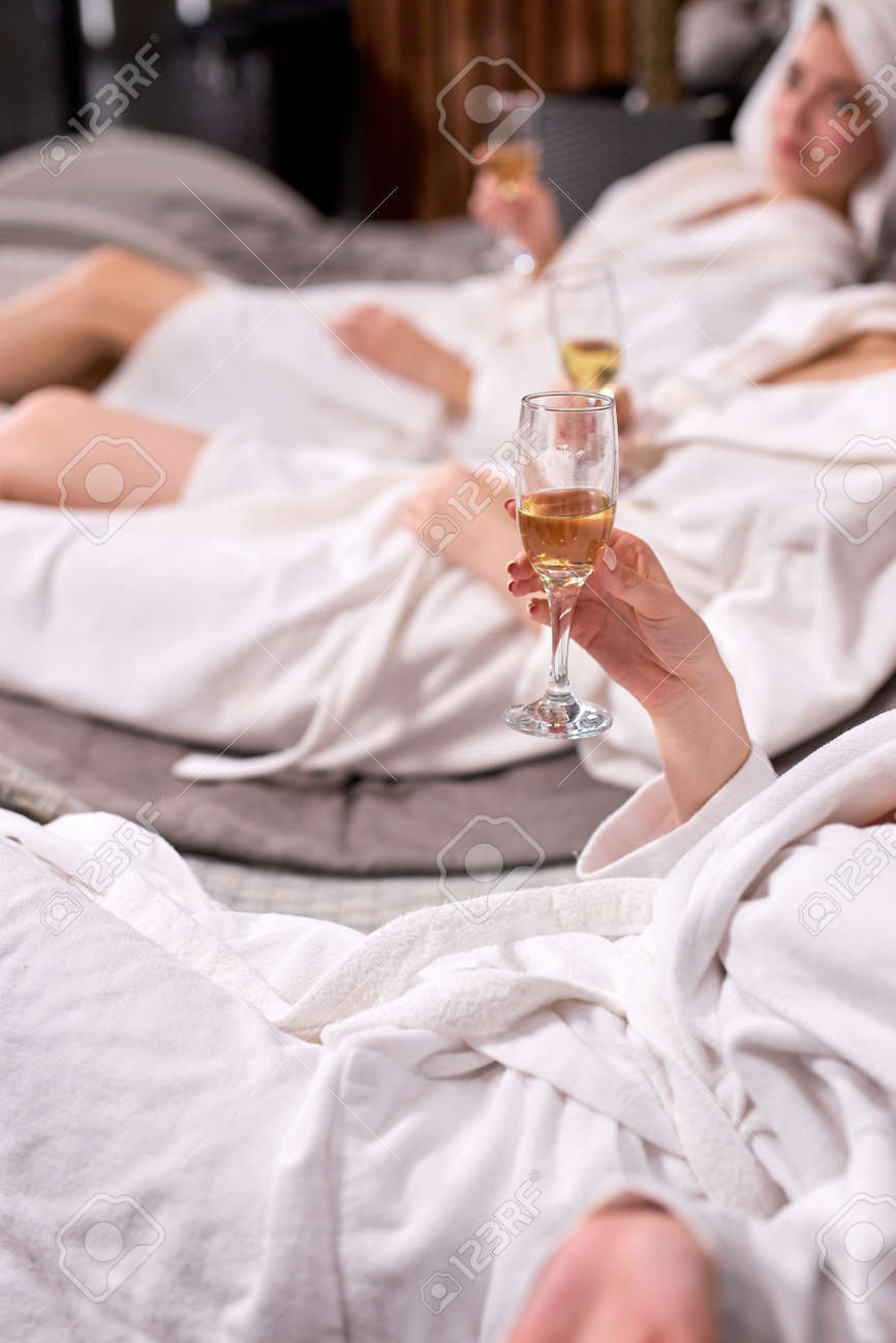 Cropped ladies in bathrobes drinking champagne after spa procedures. Spa hotel vacation concept. Cropped photo of females holding glasses. Focus on hands - 169368949