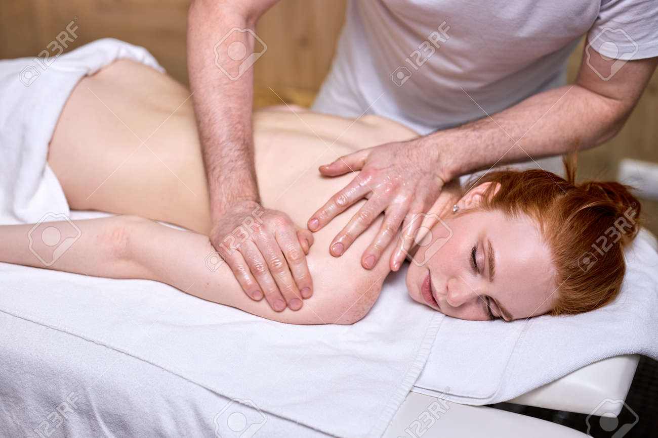 Cropped male masseur doing massage on redhead woman body in spa salon. Beauty treatment concept. Side view on shirtless female lying on stomach - 169368956