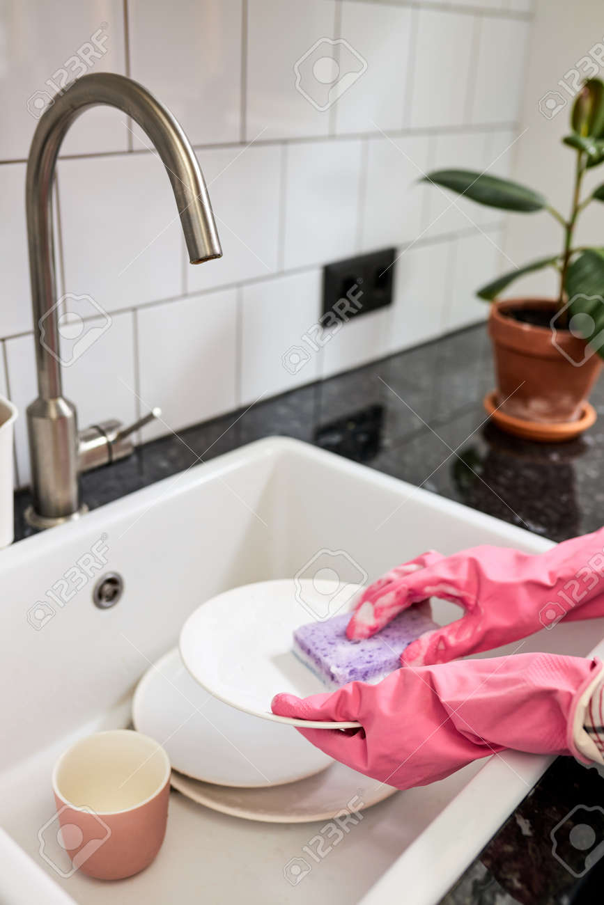 Close-up photo of female hands washing white dinner plate with sponge and foam in kitchen sink. Focus on hands in pink rubber gloves - 169369056