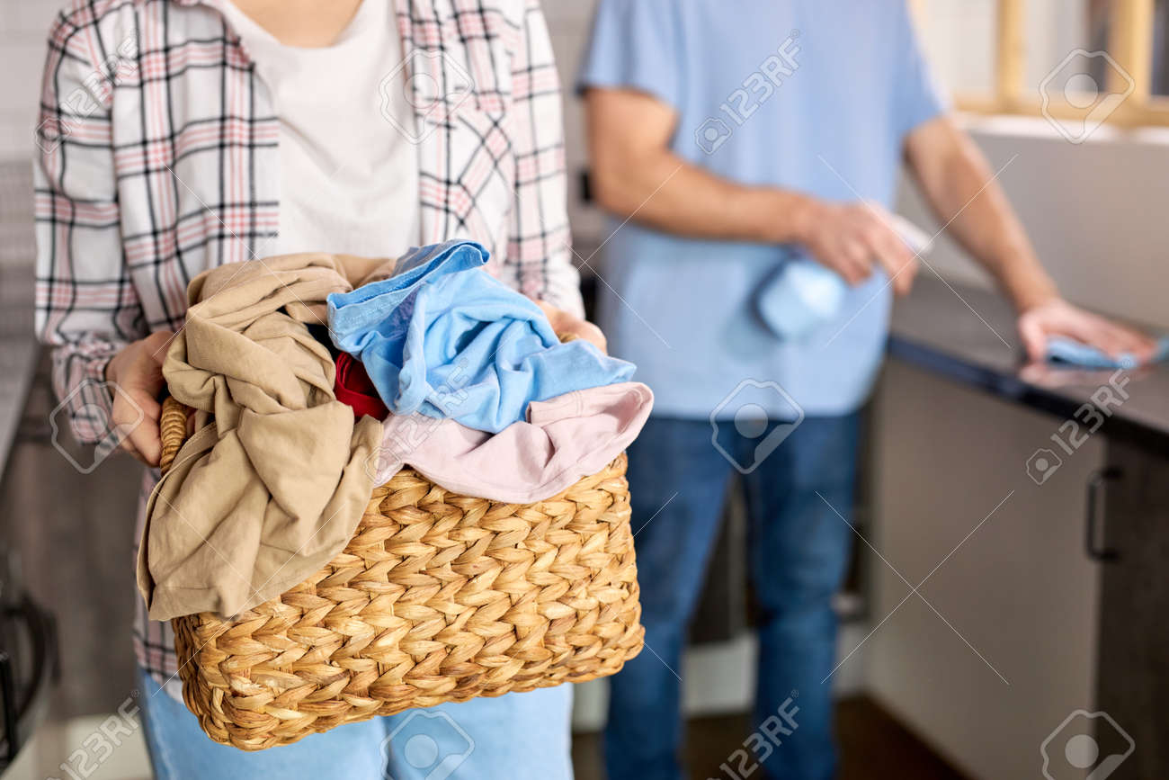 Casually dressed woman in checkered shirt holding basket full of dirty laundry needing washing, man cleaning kitchen in the background. Couple at home doing household chores, housekeeping - 169369338