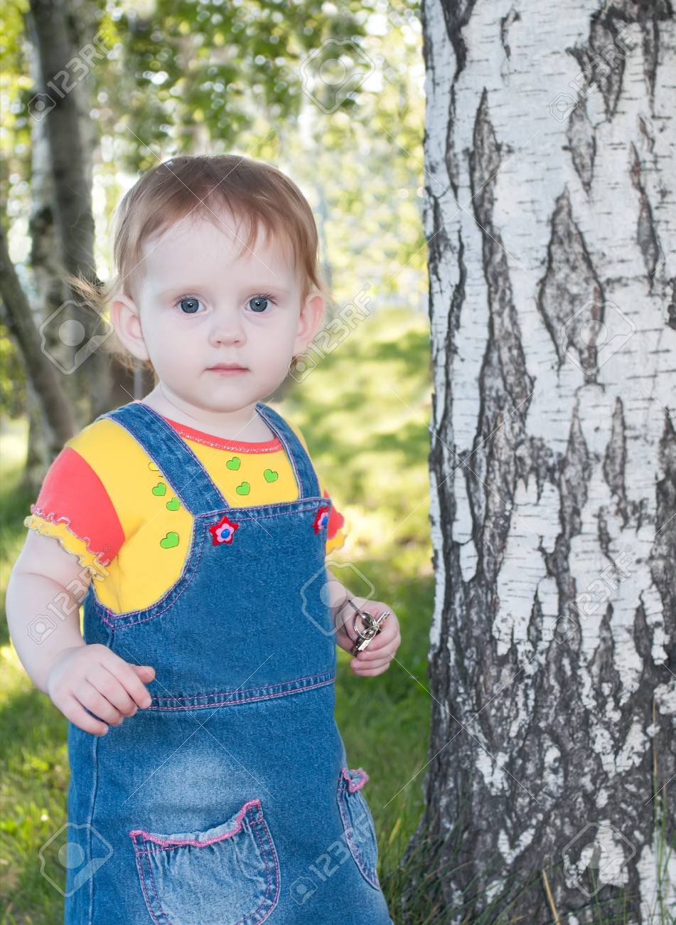 the little cute girl, standing a near birch tree Stock Photo - 17539414