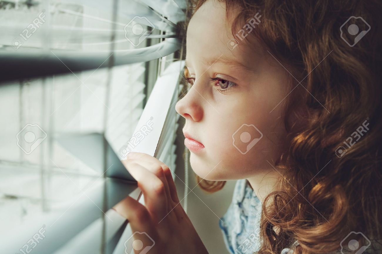 Sad little girl looking out the window through the blinds  Background