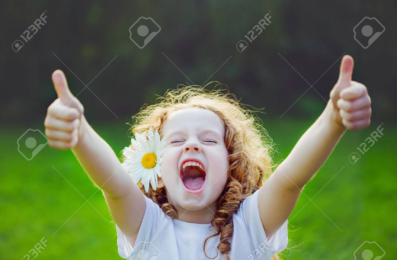 laughing girl with daisy in her hairs, showing thumbs up. stock