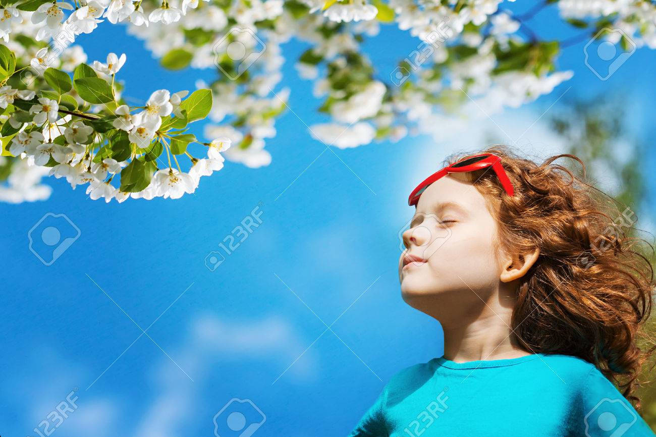 Little girl closed her eyes and breathes the fresh air in the park. - 50478384