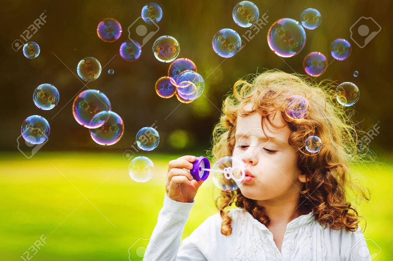 little girl blowing soap bubbles in summer park. Background toninf for instagram filter. - 52418022
