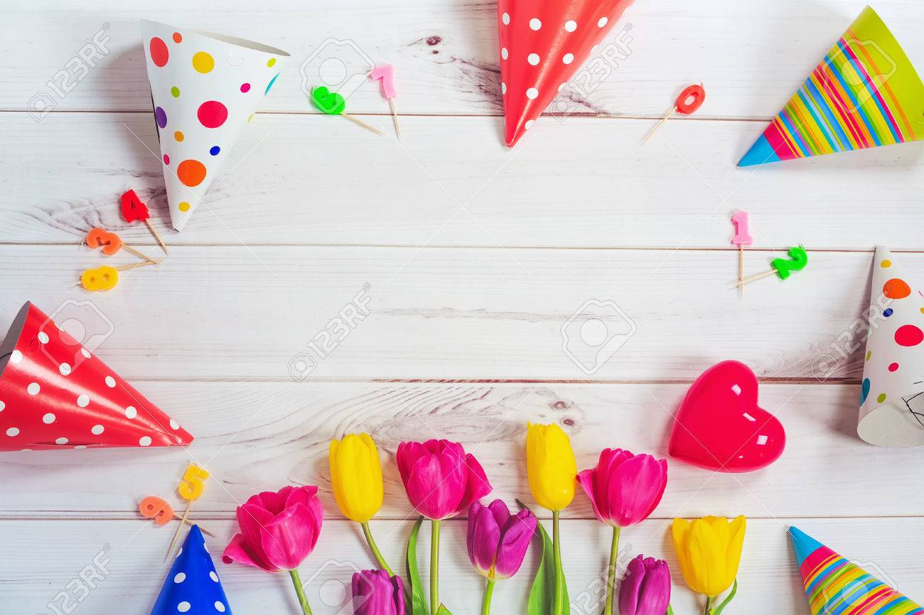 Greeting card for princess girl. Tulips, party hat, candes, red heart on wooden background. Toning instagram filter. - 55396280