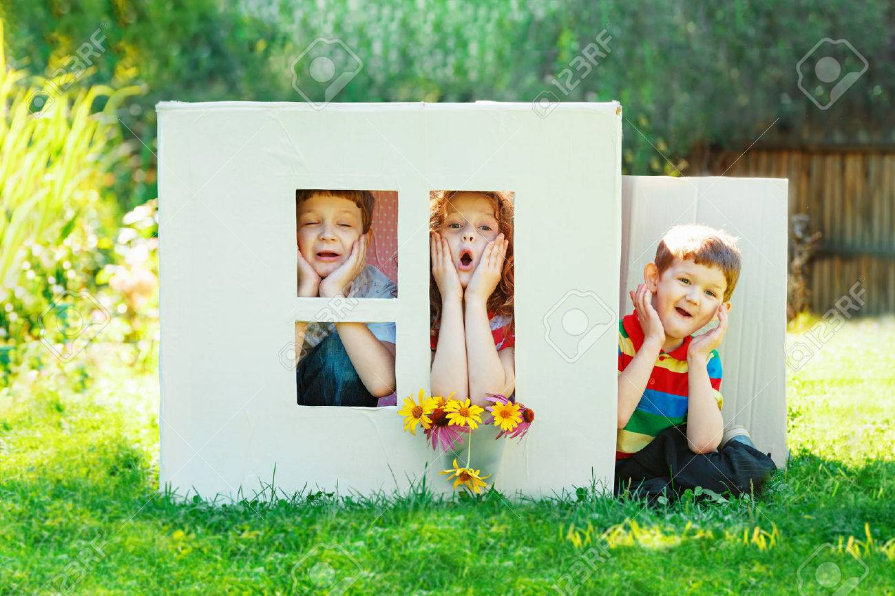 Sad children play in the house made of cardboard box. Little boy and girl dream about new home and family. - 62608687