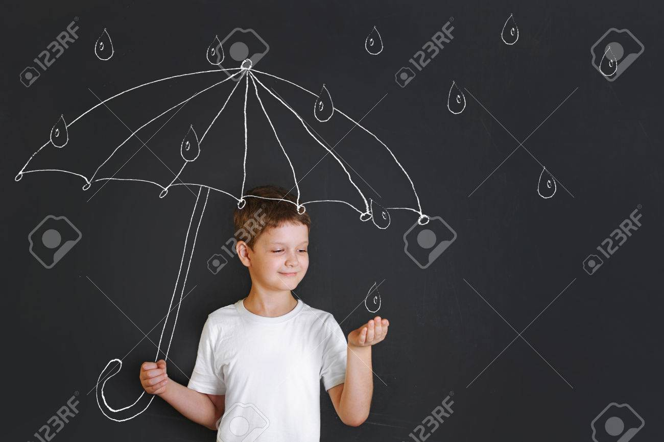 Handsome boy under chalk drawing umbrella, held out his hand and catches the raindrops. Childhood, fantasy and dreaming concept. Stock Photo - 69691887