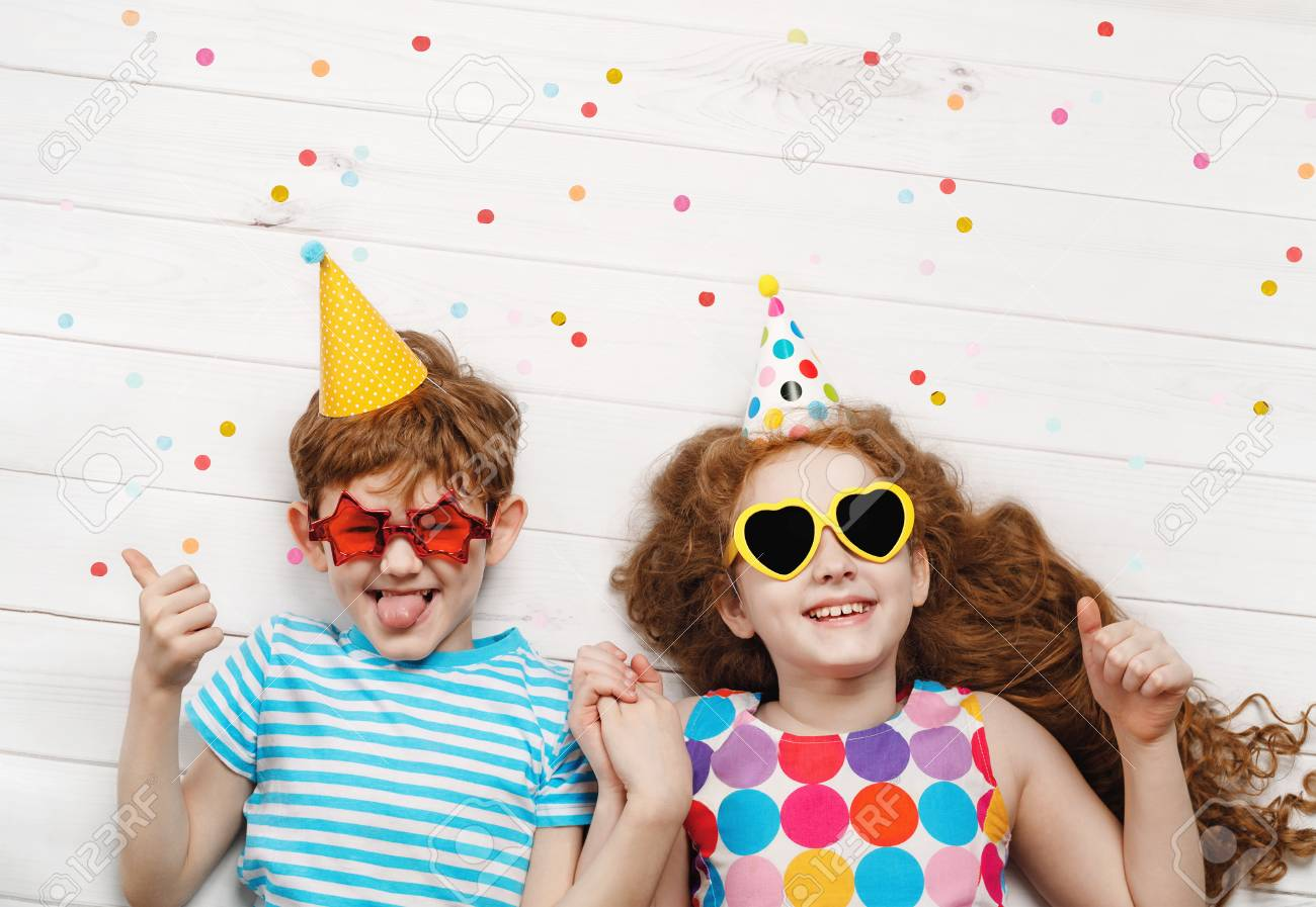 Happy children on carnival party, lying on a wooden floor. Happy childhood, Holiday concept. - 121595468