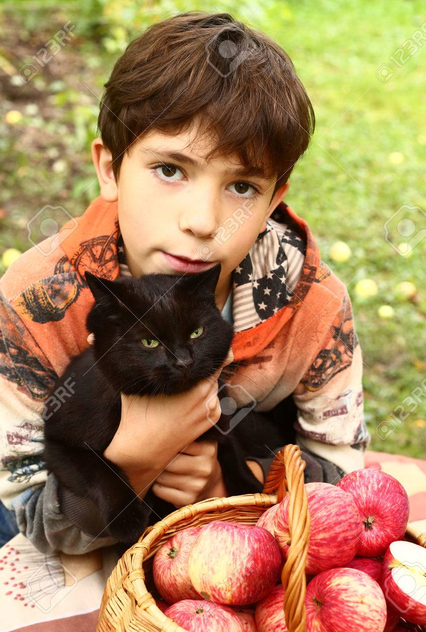 black preteen Stock Photo - preteen handsome boy with black cat and red apples close up  portrait