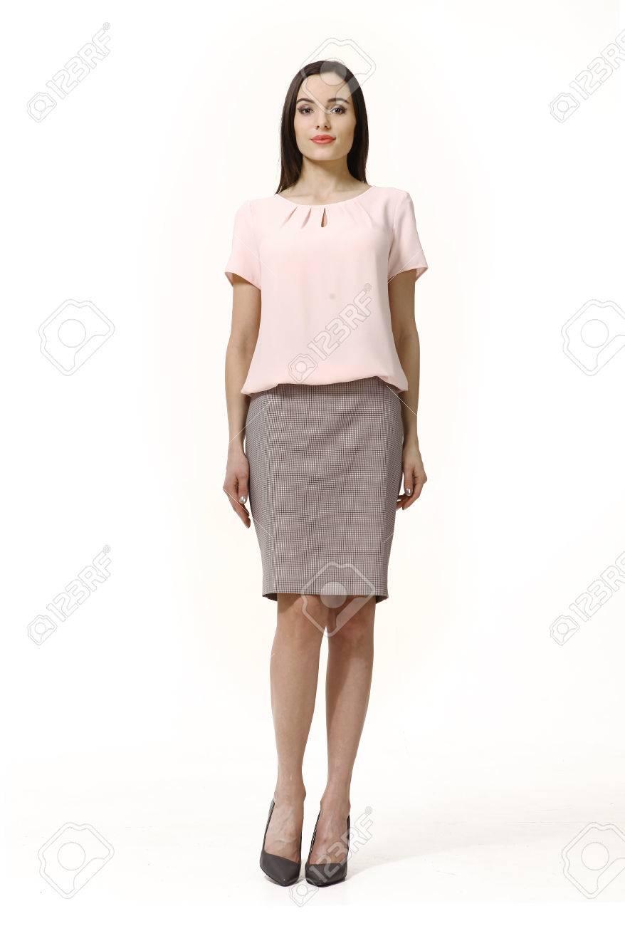 0433d62b0148fb Femme avec style cheveux raides à manches courtes blouse et jupe longueur  genou rose hauts talons longueur portrait de corps debout isolé sur blanc