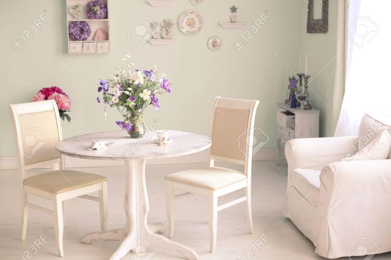 Interior comedor shabby chic con flores placas decorativas en la pared y  taza de té