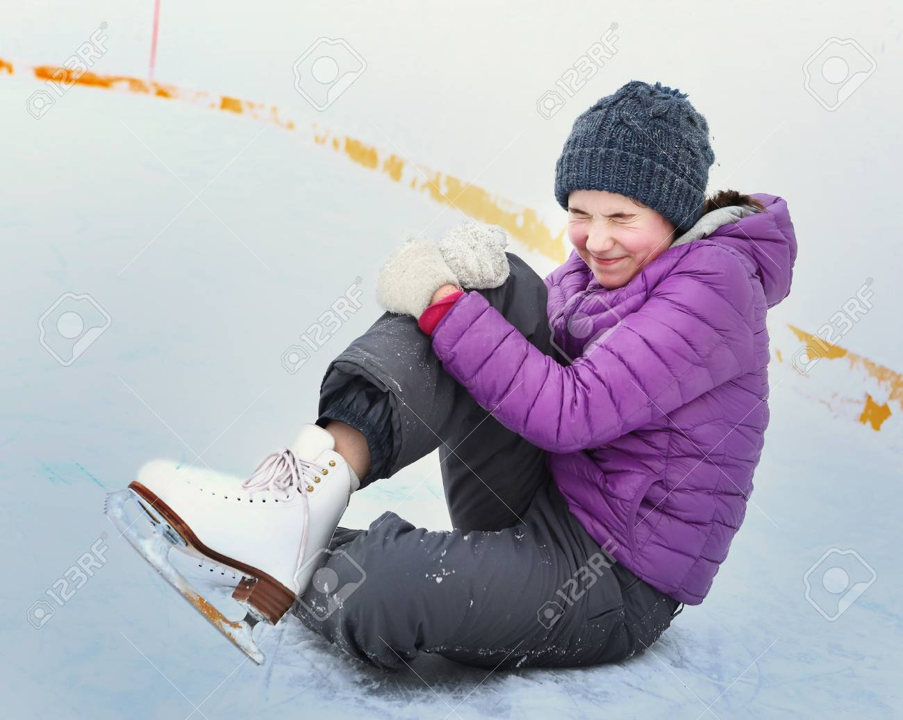 Stock Photo - teen skater girl in down jacket and knitted blue hat fall  down on skating rink hit her leg and grimace with pain