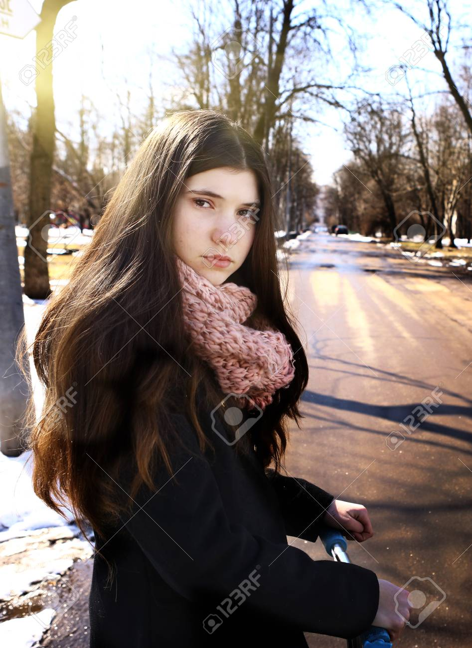 c9f96ca4c3f8 Stock Photo - teen girl in black coat and long brown hair with schooter