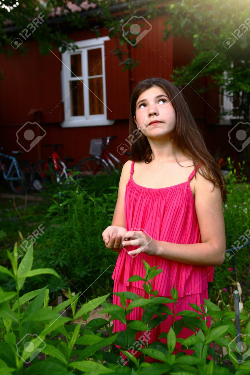 84504131b61 Stock Photo - teen girl with long brown hair in pink dress close up photo  in summer green garden on country house background