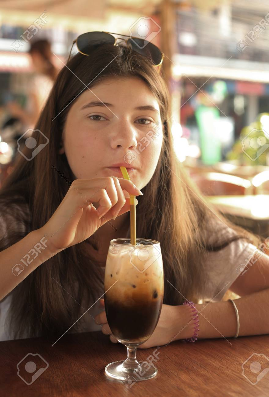 1bd0f6162ec7 Stock Photo - Young and beautiful teen cofe lover girl drink coffee  chocolate close up photo
