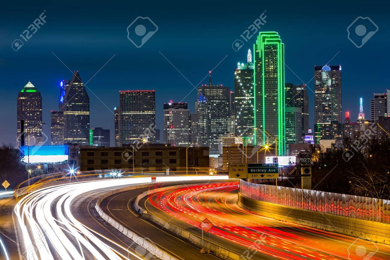 Dallas skyline by night. The rush hour traffic leaves light trails on I30 Tom Landry freeway. - 41904818