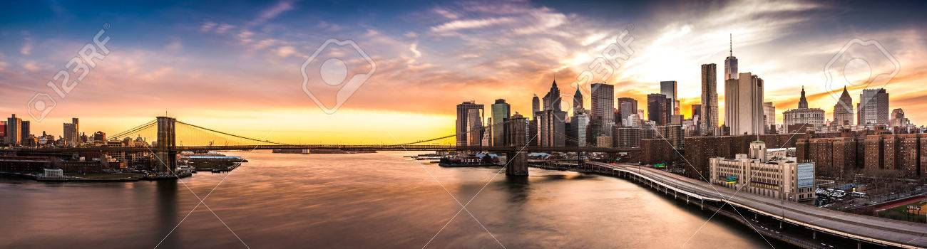 Brooklyn Bridge panorama at sunset. The iconic landmark spans between Brooklyn and the New York Financial District skyline, dominated by the Freedom Tower. - 45882424