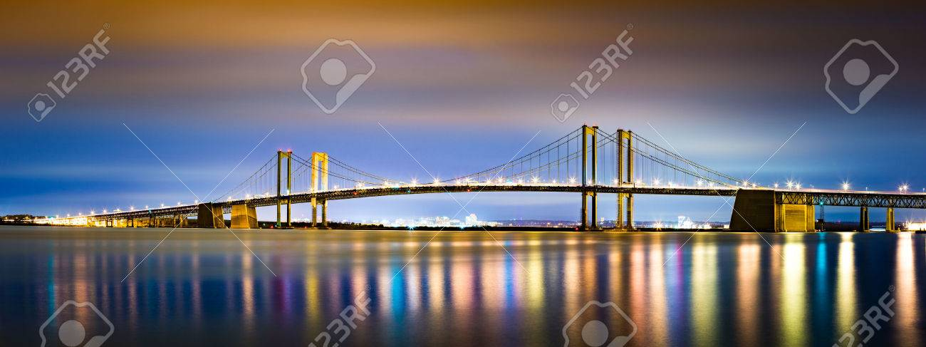 Delaware Memorial Bridge by night, viewed from New Jersey. The Delaware Memorial Bridge is a set of twin suspension bridges crossing the Delaware River between the states of Delaware and New Jersey - 47588099