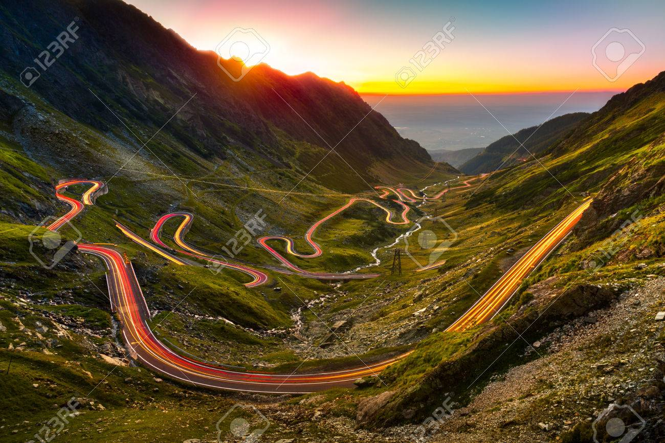 Traffic trails on Transfagarasan pass at sunset. Crossing Carpathian mountains in Romania, Transfagarasan is one of the most spectacular mountain roads in the world. - 64612907