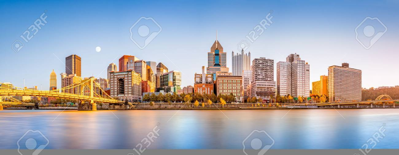 Long exposure of Pittsburgh downtown skyline and Roberto Clemente bridge, on a sunny afternoon, as viewed from North Shore Riverfront Park, across Allegheny River. - 67161982