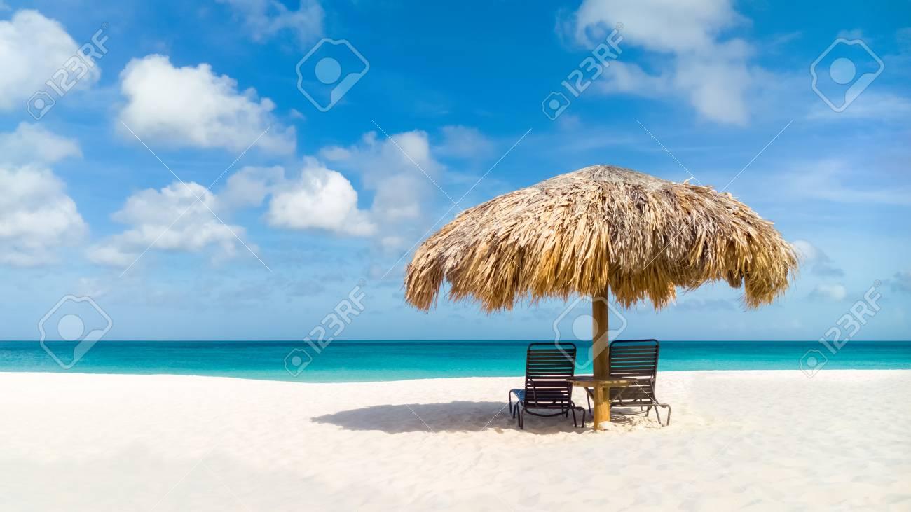Straw umbrella on Eagle Beach, Aruba on a lovely summer day - 85342913