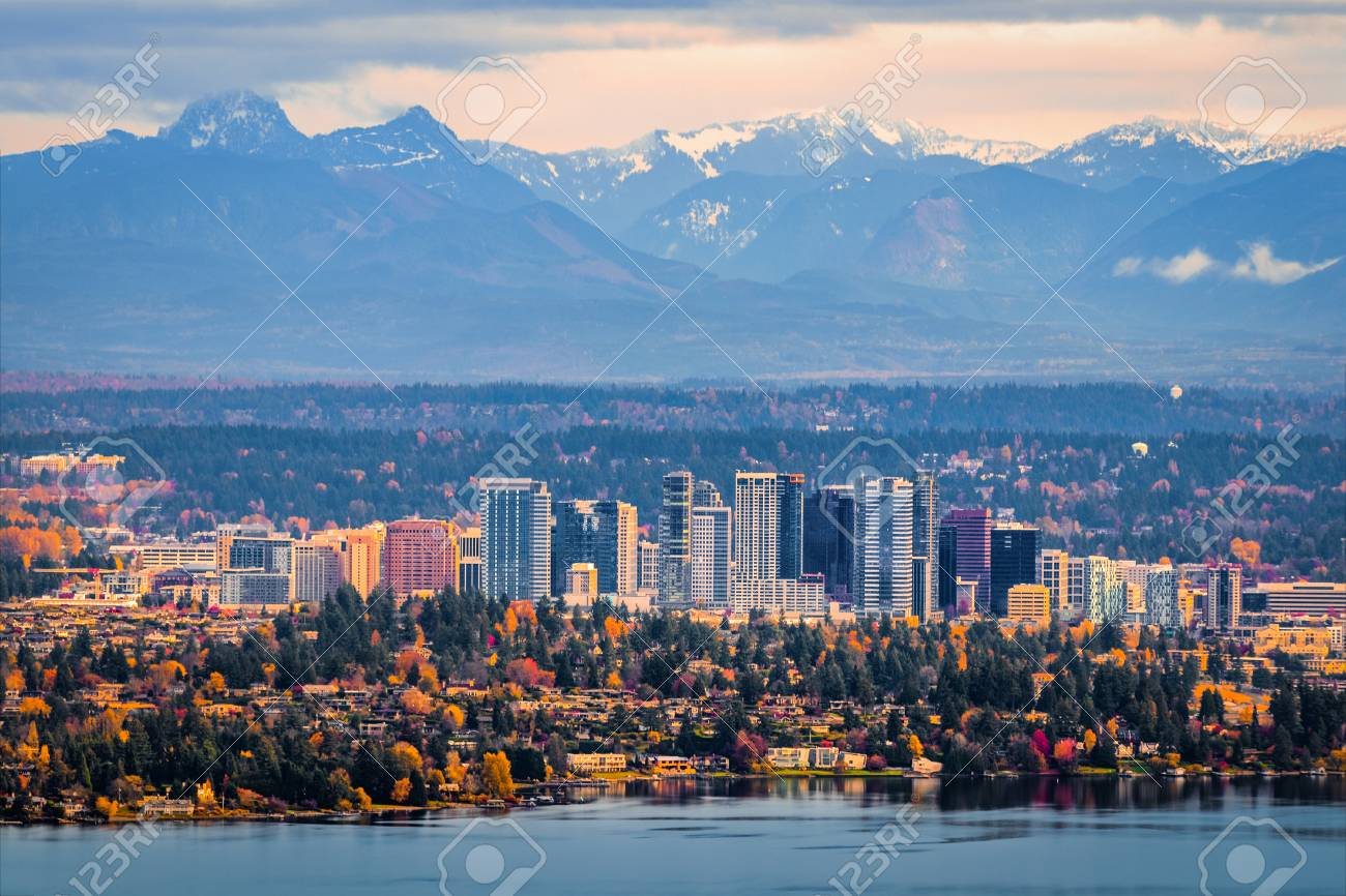 Bellevue Washington. The snowy Alpine Lakes Wilderness mountain peaks rise behind the urban skyline. - 90019213