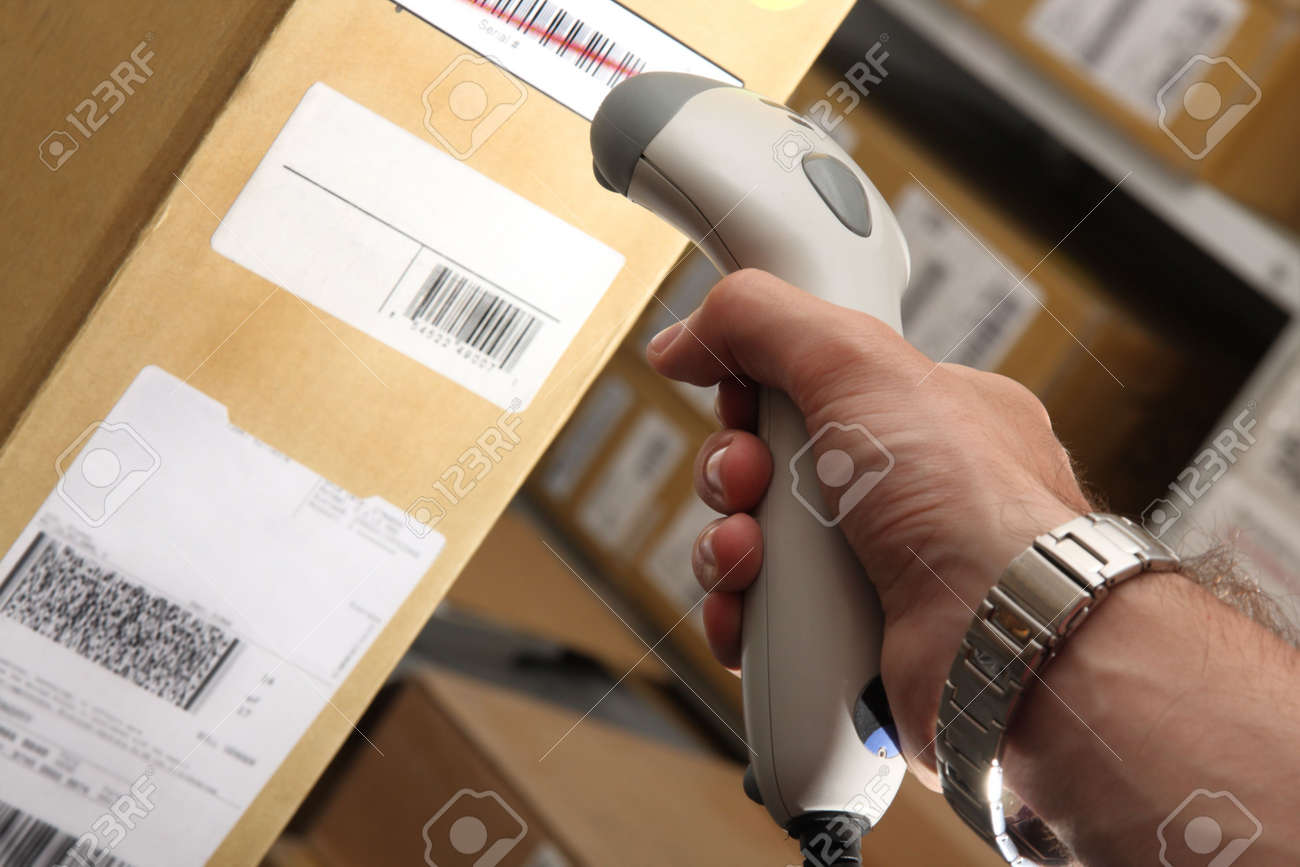 A man gets on the barcode scanner in operations directed on printed barcode. Warehouse scene. Stock Photo - 4838600