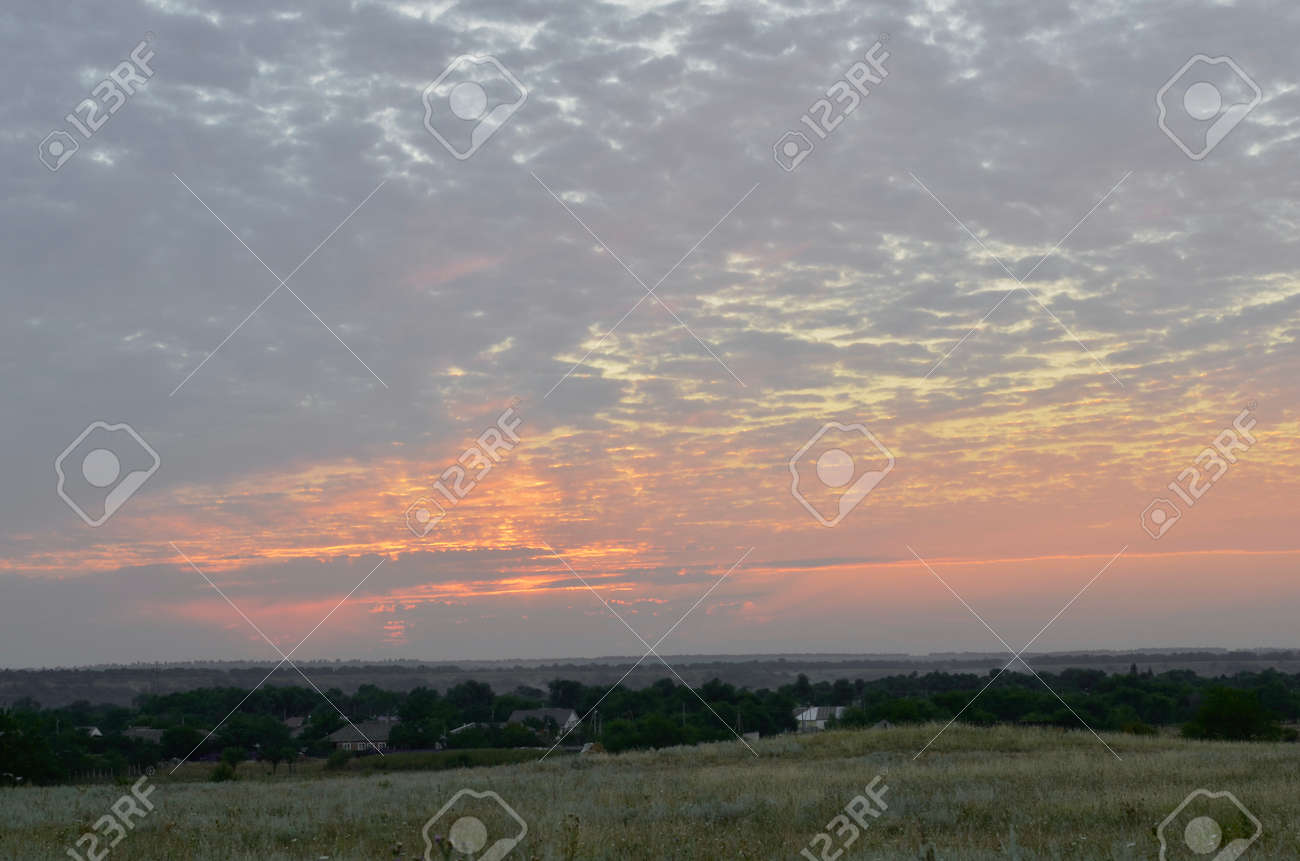 The edge of the village with small houses under a light blue sky, completely covered with clouds. During a light pink sunset. - 157839362