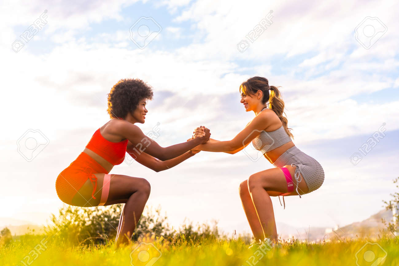 Caucasian blonde girl and dark-skinned girl with afro hair doing squat exercises in a park with the city in the background. Healthy life, fitness, fitness girls, gray and red sport outfits - 155446743