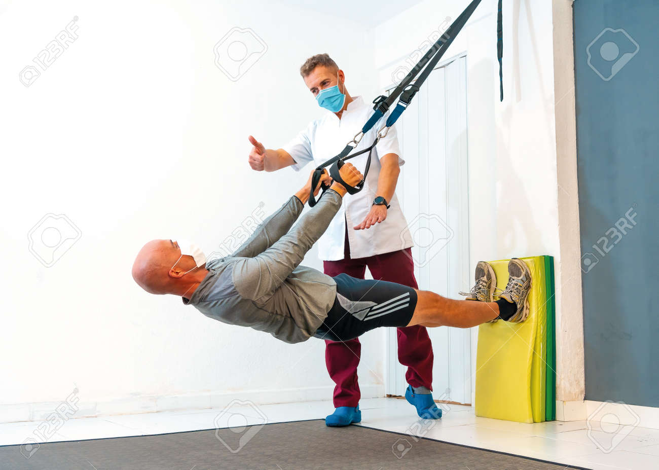 Physiotherapist with face mask and a patient exercising the body. Physiotherapy with protective measures for the Coronavirus pandemic, COVID-19. Osteopathy, sports quiromassage - 158753896
